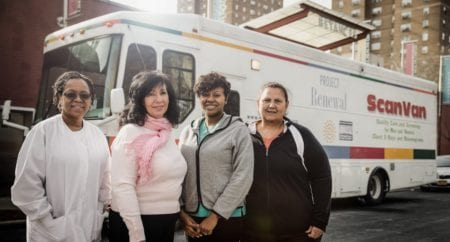Four female Project Renewal staff stand in front of a medical van